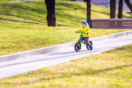 Happy little boy riding a run-bike in the park outdoor