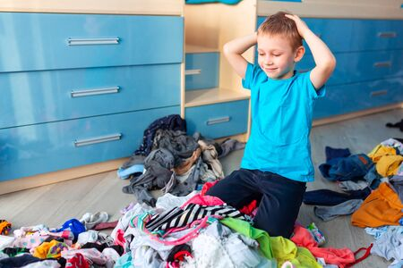Small boy desperate with the mess in his clothes in his bedroom.