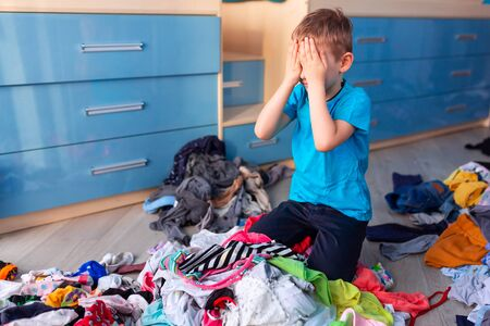 Small boy desperate with the mess in his clothes in his bedroom. Foto de archivo