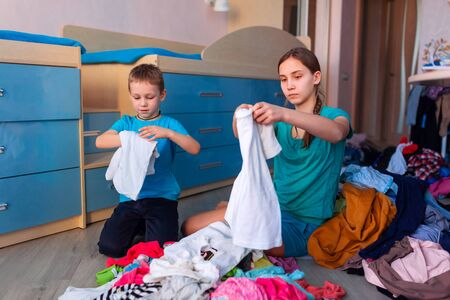 Happy children folding clothes in thier messy bedroom Imagens