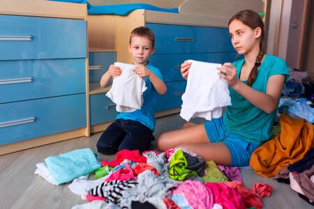 Happy children folding clothes in thier messy bedroom