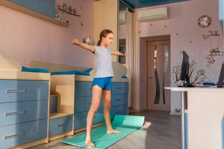 Tennage girl doing fitness gymnastics at home. Gymnastics video tutorial. Gymnastic exercises. Children's activity in quarantine during coronavirus pandemic concept Zdjęcie Seryjne