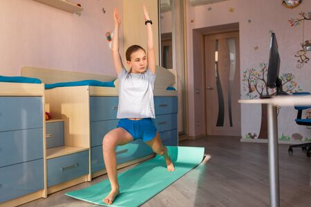 Tennage girl doing fitness gymnastics at home. Gymnastics video tutorial. Gymnastic exercises. Children's activity in quarantine during coronavirus pandemic concept