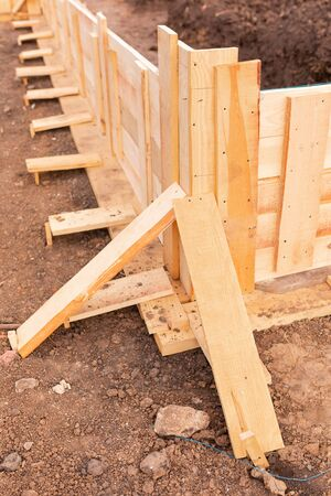 Wooden formwork for creating strip foundation for new house basis. Constructing house from the beginning concept