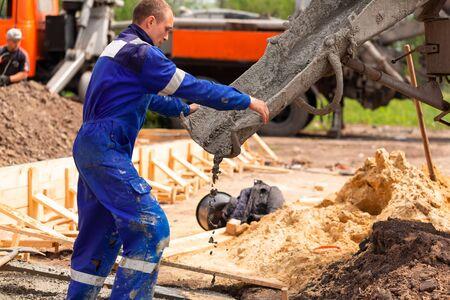 Bauarbeiter, der Zement oder Beton in die Fundamentschalung legt. Hausfundament bauen Standard-Bild