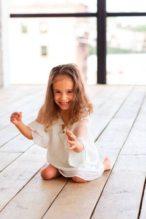 Charming little girl with infantile cerebral paralysis trying to sit and dance. Infantile cerebral paralysis disease concept