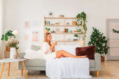 Young beautiful girl having a cup of coffee on a couch. Miracle relaxed morning concept