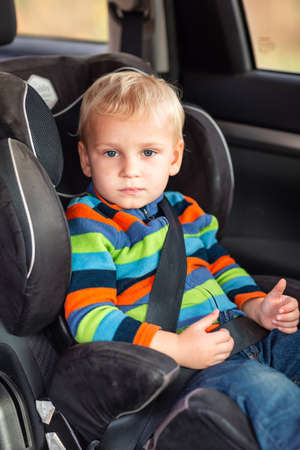 Little baby boy sitting on a car seat buckled up in the car. Children's Car Seat Safety