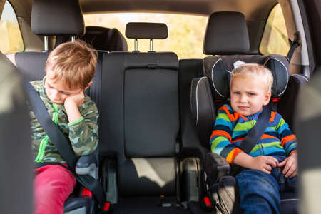 Two little boys sitting on a car seat and a booster seat buckled up in the car. Children's Car Seat Safety Foto de archivo