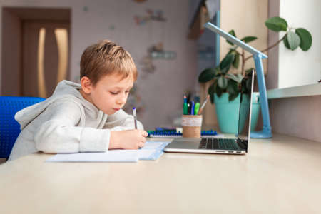 Cute little schoolboy studying at home doing school homework. Training books and notebook on the table. Distance learning online education