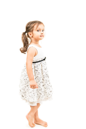 barefoot people: Cute little girl standing barefoot in profile isolated