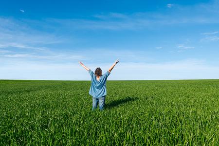 manos levantadas al cielo: Mujer con las manos levantadas de pie de nuevo en el campo verde contra el cielo azul