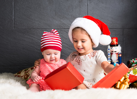opening gift: Cute little kids on rug opening a Christmas present Stock Photo