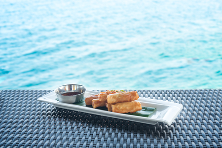 abreast: Vegetable fried spring rolls served with bittersweet sauce on wicker table and water background Stock Photo
