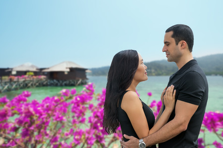 interracial love: Happy interracial couple in love at sea side with bungalow background .Summer holidays,vacation, travel and dating concept. Asian woman,Caucasian man