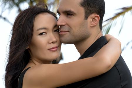 interracial love: Couple in love outdoor.Stunning sensual outdoor portrait of interracial happy couple. Asian woman,Caucasian man Stock Photo