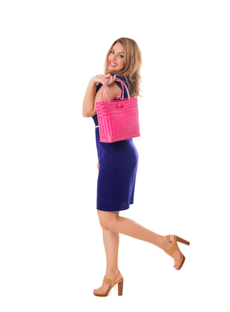 Pretty  woman in blue dress with bright wicker tote bag.Isolated on the white studio background Stock Photo
