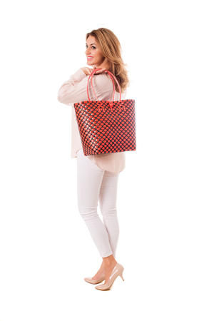 Beautiful woman in blue dress with bright wicker tote bag.Isolated on the white studio background Stock Photo