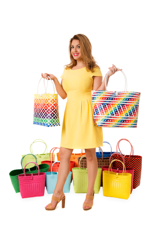 Beautiful woman in yellow dress with bright wicker tote bags.Isolated on the white studio background
