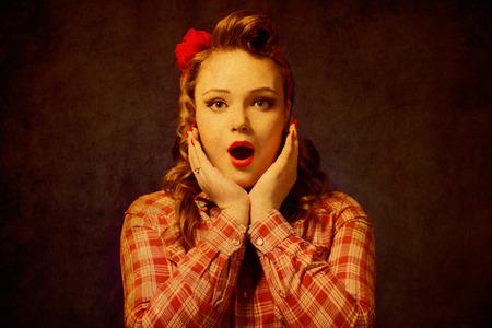Closeup joven bastante sorpresa chica pinup botón rojo camisa que le mira cámara de fondo azul estilo retro de la vendimia de los años 50. Lenguaje corporal de las emociones humanas