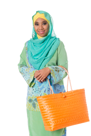 Beautiful asian muslimah woman with bright orange wicker tote bags. Isolated on the white studio background Stock Photo