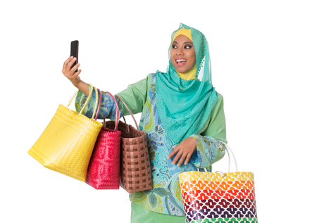 Beautiful asian muslimah woman with bright wicker tote bags taking selfie. Isolated on the white studio background