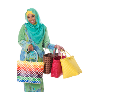 Beautiful asian muslimah woman with bright wicker tote bags. Isolated on the white studio background.Copyspace