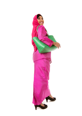 Beautiful asian muslimah woman with green wicker tote bag. Isolated on the white studio background