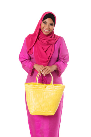 Happy asian muslimah woman with yellow wicker tote bag. Isolated on the white studio background Stock Photo