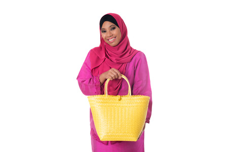 Beautiful asian muslimah woman with yellow wicker tote bag. Isolated on the white studio background Stock Photo