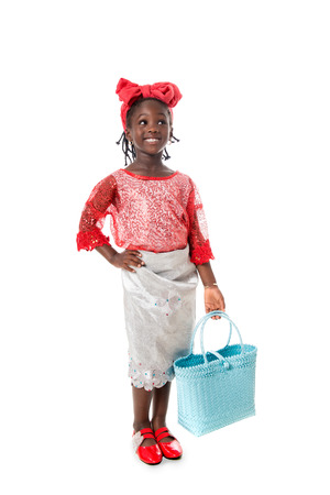 Beautiful portrait of a happy African  little girl smiling  with wicker blue tote bag in traditional costume on white background.Studio shot Stock Photo