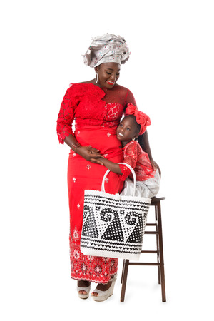 Beautiful African woman and little girl  in traditional clothing with wicker tote bag. Isolated on the white studio background Stock Photo