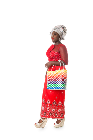 Beautiful African woman walking in traditional red clothing with bright wicker tote bag. Isolated on the white studio background