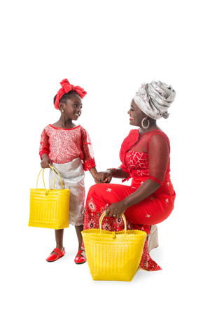 Beautiful African woman and little girl in traditional red clothing with bright yellow wicker tote bags. Isolated on the white studio background