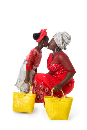 Mother and child girl kissing in traditional red clothing with yellow wicker tote bags. Isolated on the white studio background Stock Photo
