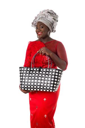 枝編み細工品のトートバッグと伝統的な服で美しいアフリカ女性。ホワイト スタジオの背景に分離