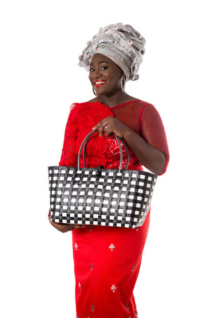 Beautiful African woman in traditional clothing with wicker tote bag. Isolated on the white studio background Фото со стока