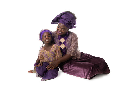 Beautiful African woman and lovely little girl sitting on floor in traditional purple costume on white background.Studio shot Stock Photo