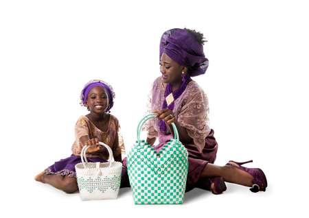 Beautiful African woman and little girl in traditional purple clothing with wicker tote bags sitting on the floor. Isolated on the white studio background Stock Photo