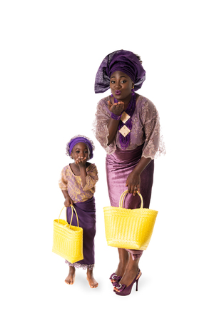 africa kiss: Beautiful African woman and little girl in traditional purple clothing with yellow wicker tote bags showing air kiss. Isolated on the white studio background