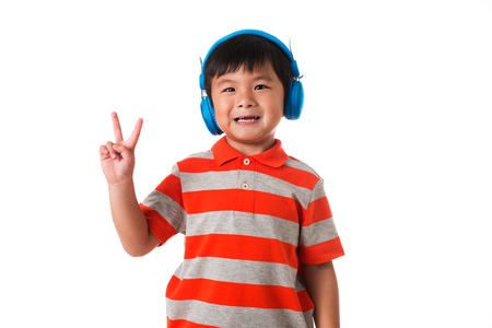 Music and technology concept.Asian little boy with headphone showing two fingers or victory gesture on white background Stock Photo
