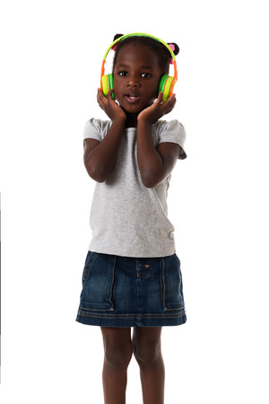 audio book: Music and technology concept.African lovely little girl   with headphone singing.Studio shot on white background