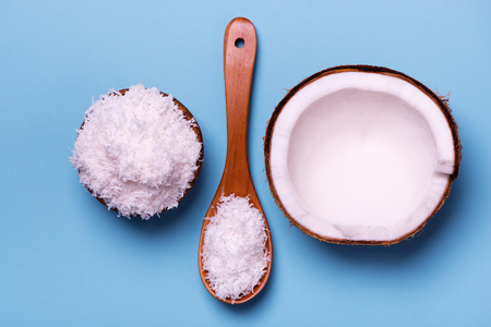 top view of coconut flakes in wooden bowl, wooden spoon and half of the coconut isolated over blue background Banque d'images - 99894343