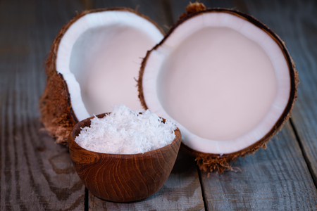 coconut split in two halves and flakes in wooden bowl