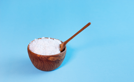 coconut flakes in wooden bowl with spoon, isolated over blue background Banque d'images - 99911758