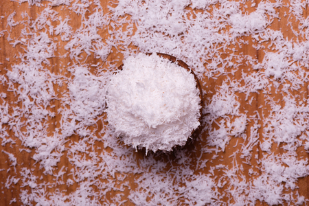top view of coconut flakes in a bowl on a wooden table Banque d'images - 99911086