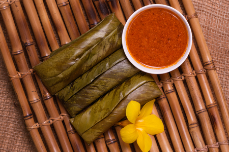 sticky rice wrapped in leaves and served with peanut sauce. Famous cuisine in Borneo. Brunei, Sarawak and Sabah. Called Kelupis.