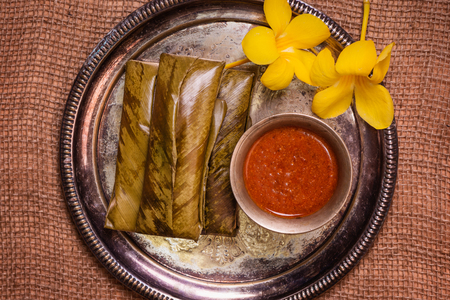 top view of sticky rice wrapped in leaves and served with peanut sauce. Famous cuisine in Borneo. Brunei, Sarawak and Sabah. Called Kelupis. Stock Photo