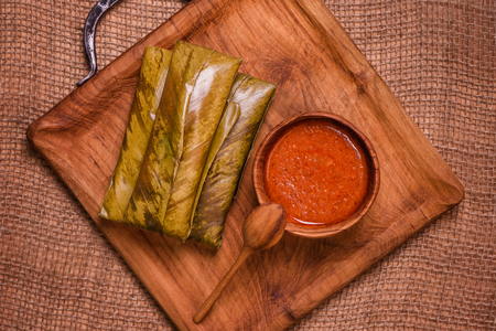 top view of sticky rice wrapped in leaves and served with peanut sauce on a wooden plate. Famous cuisine in Borneo. Brunei, Sarawak and Sabah. Called Kelupis. Stock Photo