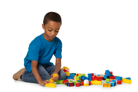 Little african american boy playing on the floor with lots of colorful plastic blocks in studio, isolated on white background